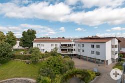 Ansicht des Pflegeheims Sankt Veronika vom Innenhof des Seniorenzentrums aus gesehen mit grünen Bäumen umrahmt