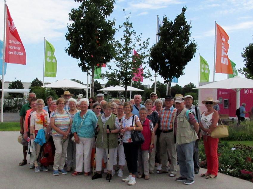 Gruppenbild der Senioren beim Seniorenausflug des Frohen Alters Dunningen und Lackendorf zur Bundesgartenschau in Heilbronn auf dem Gelände der BUGA mit gehissten Fahnen im Hintergrund