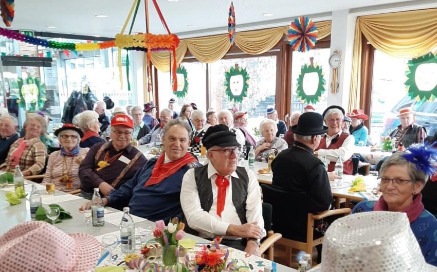 verkleidete fröhliche Senioren die an Tischen sitzen in der Cafeteria des Seniorenzentrums Haus am Adlerbrunnen bei der Seniorenfasnacht